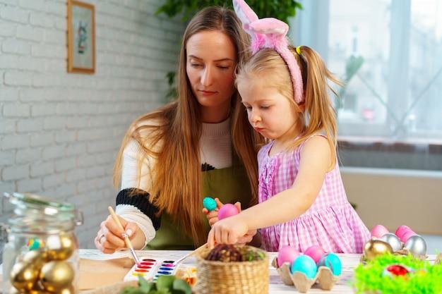 Linda familia, madre e hija preparándose para la celebración de pascua