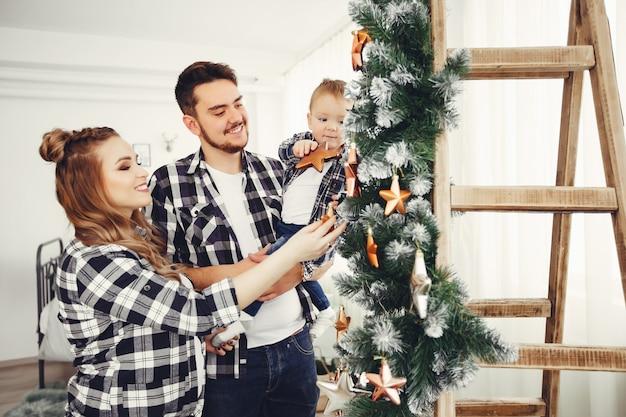 Linda familia de pie cerca del árbol de navidad