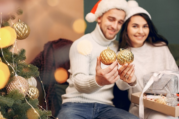 Linda familia sentada en casa cerca del árbol de navidad