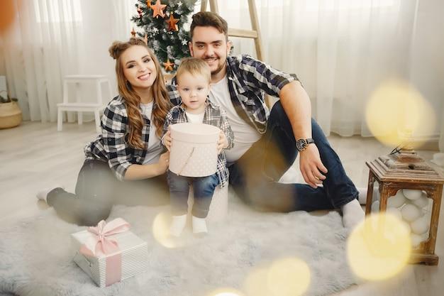 Linda familia sentada cerca del árbol de navidad