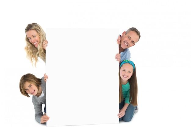 Linda familia sonriendo a la cámara sosteniendo el cartel