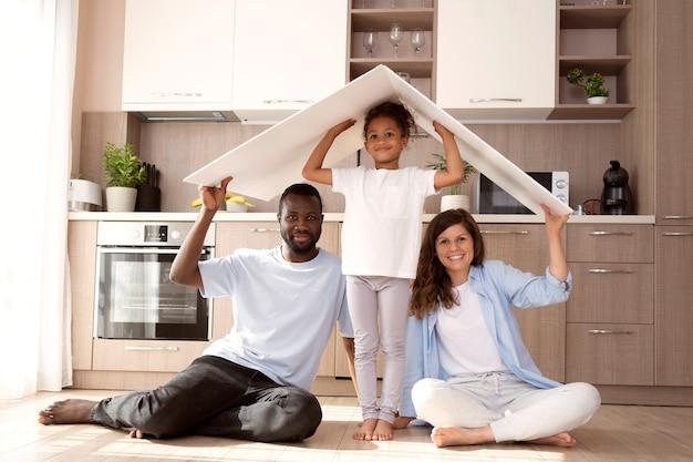 Linda familia sosteniendo un techo sobre su cabeza