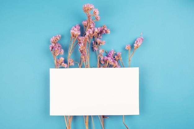 Linda flor seca de violeta seca con tarjeta blanca en la parte superior