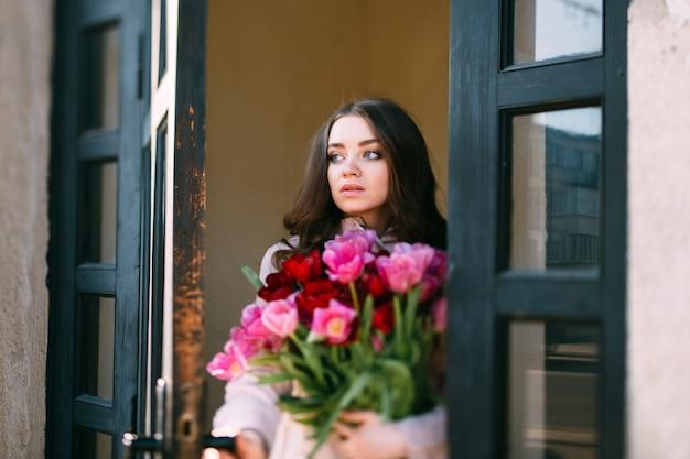 Linda hembra joven con flores abriendo la puerta y mirando