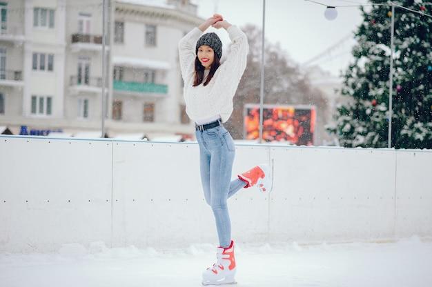 Linda y hermosa chica en un suéter blanco en una ciudad de invierno