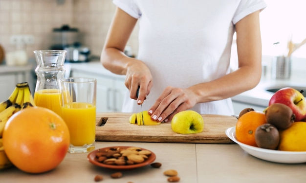 Linda hermosa y feliz joven morena en la cocina de casa está cortando una manzana