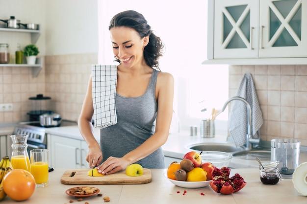 Linda hermosa y feliz joven morena en la cocina de casa está cortando manzanas