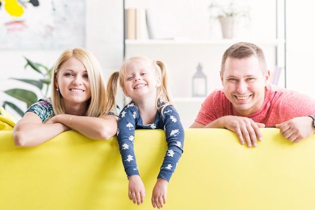 Linda hija sonriente con sus padres sentados en el sofá