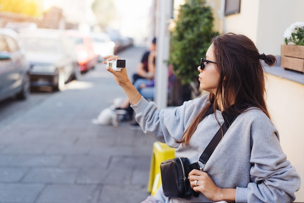 Linda, joven blogger femenina posando en la cámara.