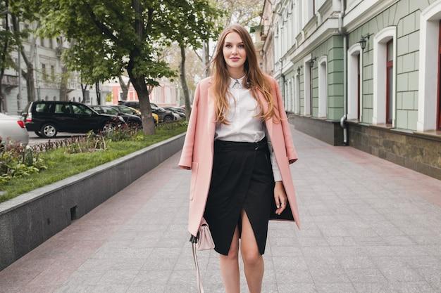 Linda joven y elegante hermosa mujer caminando en la calle, vestida con abrigo rosa, bolso, camisa blanca, falda negra, traje de moda, tendencia de otoño, sonriendo feliz, accesorios