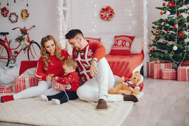 Linda joven familia sentada en casa en una cama