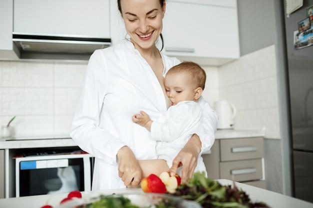 Linda joven madre amamanta al bebé mientras cocina un desayuno saludable
