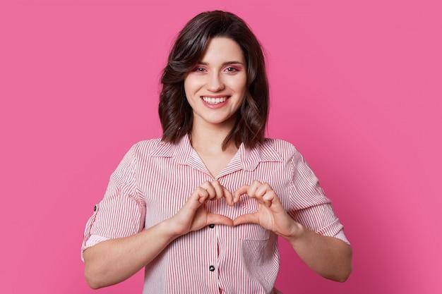 Linda joven modelo enamorada muestra corazón con sus propias manos.