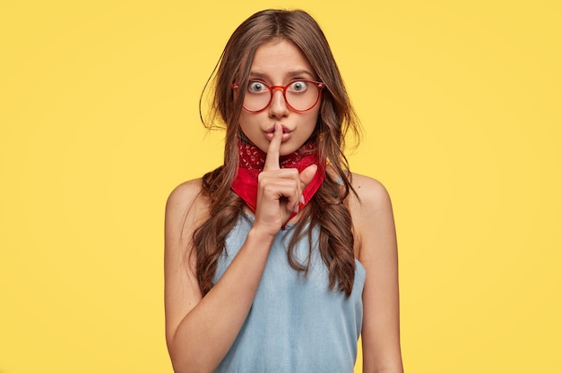 Linda joven morena con gafas posando contra la pared amarilla
