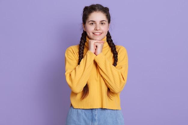 Linda joven mujer joven con sonrisa encantadora, mirando a cámara y manteniendo los puños debajo de la barbilla