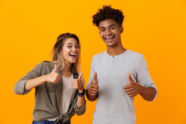 Linda joven pareja amorosa posando aislada sobre pared amarilla mostrando los pulgares para arriba