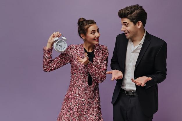 Linda joven pareja de personas en trajes de fiesta divirtiéndose y comunicándose contra la pared violeta