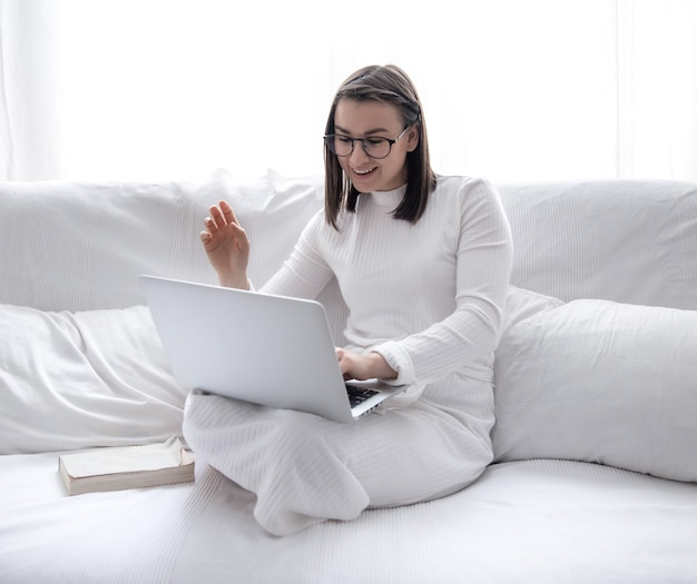Una linda joven está sentada en su casa en un sofá blanco con un vestido blanco y trabajando en una computadora portátil.