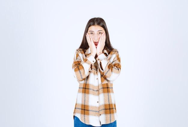Linda joven sosteniendo las mejillas con las manos.