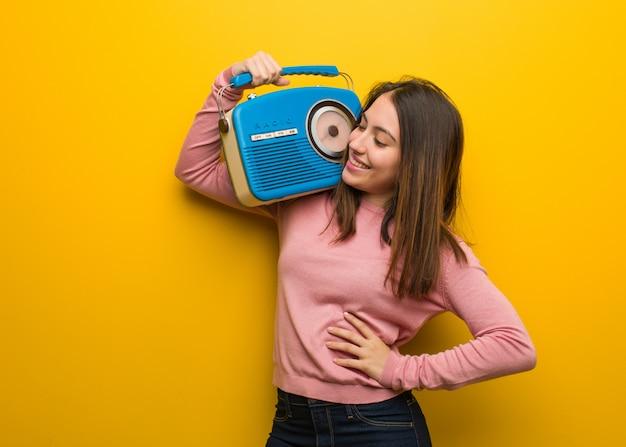 Linda joven sosteniendo una radio vintage sonriendo confiados