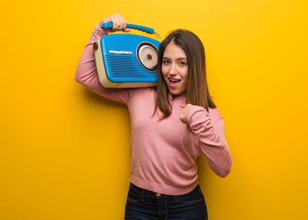 Linda joven sosteniendo una radio vintage sorprendida, se siente exitosa y próspera