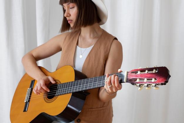 Linda joven tocando la guitarra en el interior