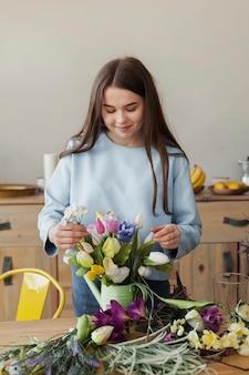 Linda jovencita ajustando un jarrón con flores