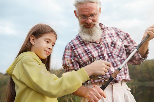 Linda jovencita disfrutando de aprender sobre la pesca de su abuelo