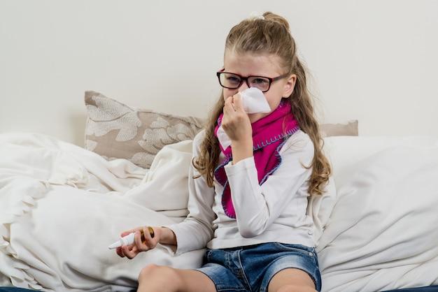 Linda jovencita en gafas estornudando en un pañuelo