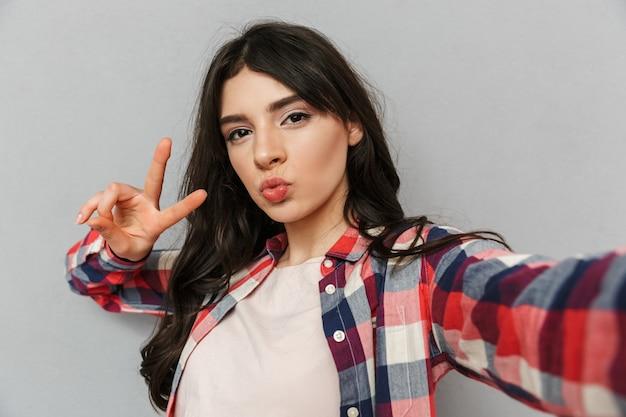 Linda jovencita hermosa hacer selfie mirando la cámara hacer gesto de paz.