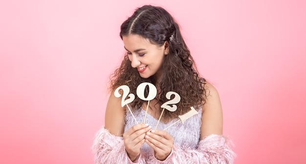 Linda jovencita morena con cabello rizado y hombros desnudos tiene número de madera para el nuevo año en sus manos sobre un fondo rosa