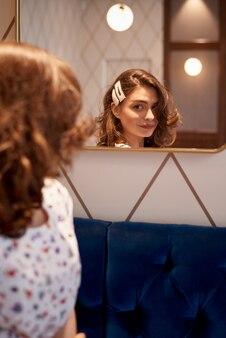 Linda jovencita sonriendo y mirándose en el espejo