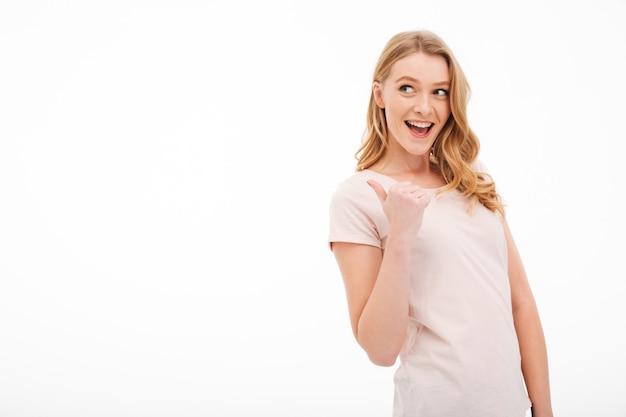 Linda jovencita sonriente señalando.