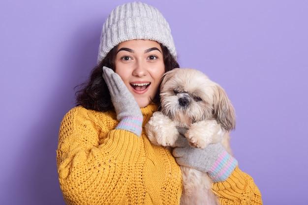 Linda jovencita sosteniendo y abrazando a su cachorro, mujer de cabello oscuro mirando con la boca abierta y manteniendo la palma en su mejilla