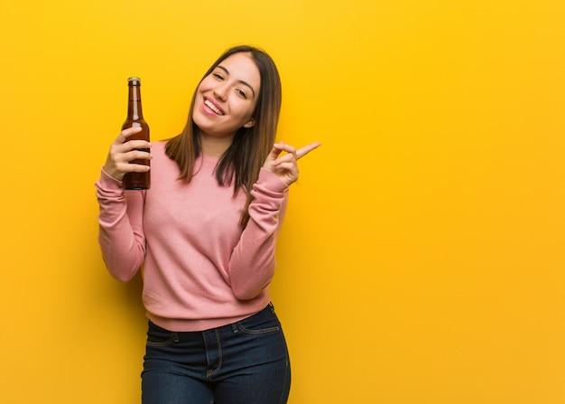 Linda jovencita sosteniendo una cerveza apuntando hacia el lado con el dedo