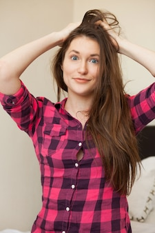 Linda jovencita sosteniendo su cabello