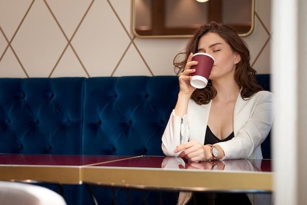 Linda jovencita tomando café en la cafetería