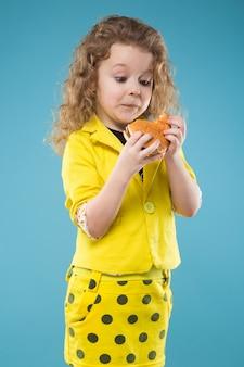 Linda jovencita vestida de amarillo con hamburguesa.