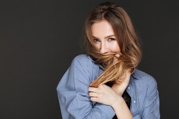 Linda juguetona joven cubierto rostro con su cabello