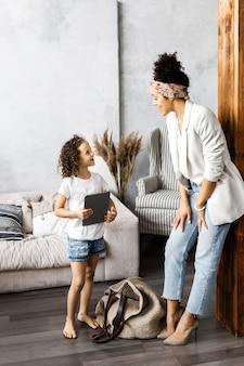 Linda madre e hija hablan y miran la tableta mientras están de pie en la sala de estar