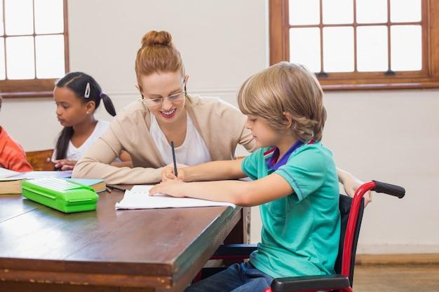 Linda maestra ayudando al alumno en el aula en la escuela primaria