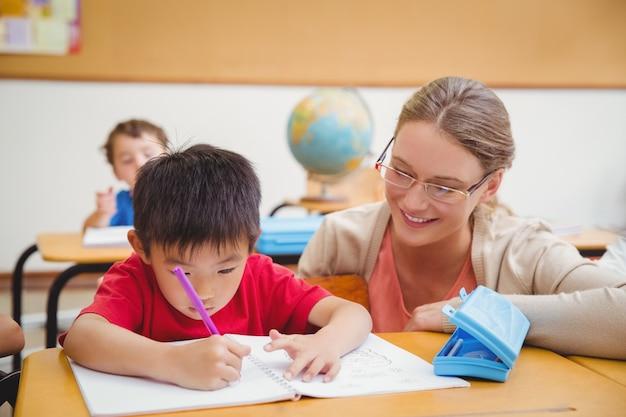 Linda maestra ayudando a los alumnos en el aula