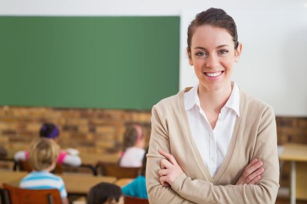 Linda maestra sonriendo a la cámara en la parte posterior del aula