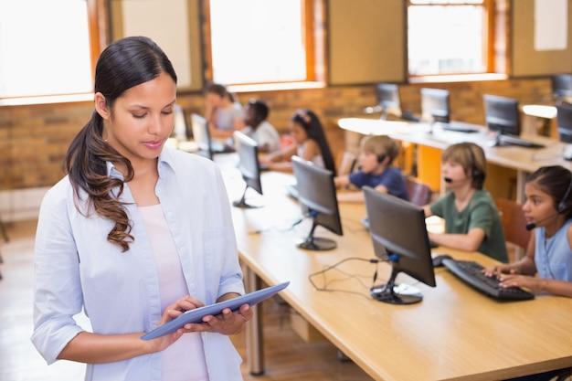 Linda maestra con tableta en clase de informática