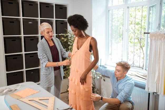 Linda modelo con cabello rizado de pie en un taller y mirando su nuevo vestido de verano