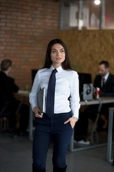 Linda morena es una oficinista que está de pie en la oficina, sosteniendo una computadora portátil, dos colegas están trabajando detrás de ella.
