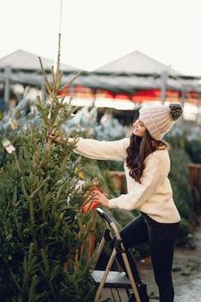 Linda morena en un suéter blanco con arbol de navidad.