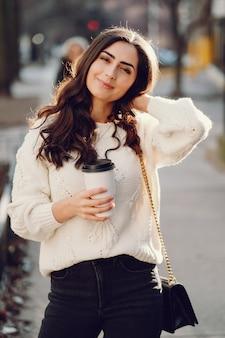 Linda morena en un suéter blanco en una ciudad