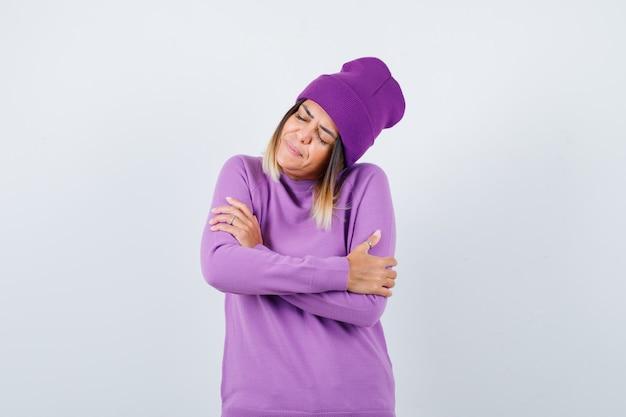 Linda mujer abrazándose a sí misma, manteniendo los ojos cerrados en suéter, gorro y luciendo relajada. vista frontal.