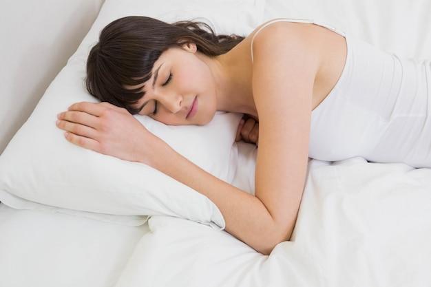 Linda mujer acostada en la cama profundamente dormida